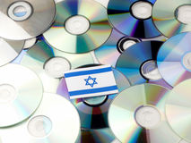 Israeli flag on top of CD and DVD pile isolated on white. Israeli flag on top of CD and DVD pile isolated Royalty Free Stock Images