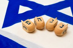 Israeli Flag with Wooden Dreidels. A white and blue Israeli Flag with the star of david on it with wooden dreidels for the Jewish holiday of Hanukkah