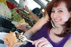 Israeli girl. Eating Falafel, while talking on the mobile phone Stock Photo