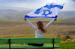 Israeli jewish little girl with Israel flag back view. Beautiful young jewish girl sitting holding Israel flag in the wind and enjoying great view landscape on stock images