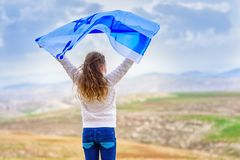Israeli jewish little girl with Israel flag back view. Little patriot jewish girl standing and enjoying with the flag of Israel on blue sky background.Memorial royalty free stock photo