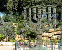 Israeli Knesset Menorah bronze statue with relief sculptures. The Knesset Menorah in Jerusalem stands on a rock plaza with rocks and gardens in the background Stock Images