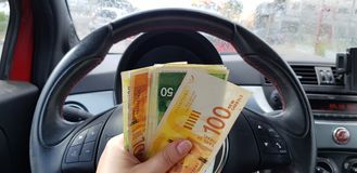 Israeli new shekels banknotes of 100, 50 in female hand inside sport car royalty free stock image