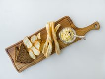 Israeli moussaka with bread chips on a board on a white table. stock image