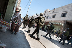 Israeli Occupation Soldiers in Hebron. HEBRON, OCCUPIED PALESTINIAN TERRITORIES - JULY 12: Israeli soldiers occupying Hebron's streets pass an elderly royalty free stock photos