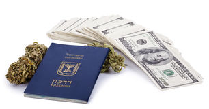 Drug Trafficking Pays Well. An Israeli passport, two Marijuana buds and a large stack of 100 US dollar money notes  on white background Royalty Free Stock Photo
