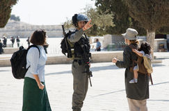 Israeli police officer. JERUSALEM, ISRAEL - OCT 08: Israeli police officer tells tourists to go backward on the temple-square in Jerusalem during religious Stock Image