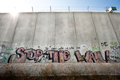 Israeli Separation Wall. The graffiti slogan Stop the Wall is painted on the Israeli separation barrier's 8 meter tall concrete wall around the West Bank town of Royalty Free Stock Photo