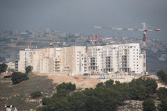 Israeli settlement in occupied Palestinian territory. Construction cranes tower over expansion of Har Homa, an Israeli settlement build on land taken from the Royalty Free Stock Photo