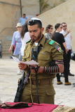 Israeli soldier prays by the Western Wall at the Old City of Jerusalem. JERUSALEM, ISRAEL - APRIL 30, 2017: Religious Jews pray by the Western Wall inside of Royalty Free Stock Photos