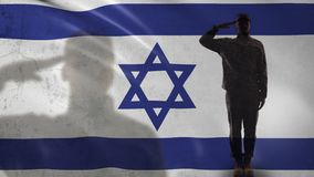 Israeli soldier silhouette saluting against national flag, terrorism prevention. Stock footage stock video footage