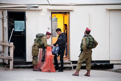Israeli Soldiers at Hebron Checkpoint. HEBRON, OCCUPIED PALESTINIAN TERRITORIES - OCTOBER 27: Israeli soldiers search a Palestinian youth's backpack at a Stock Image