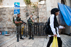 Israeli Soldiers in Jerusalem. EAST JERUSALEM, OCCUPIED PALESTINIAN TERRITORIES - SEPTEMBER 4: A Palestinian woman passes soldiers of the Israeli Border Police stock images