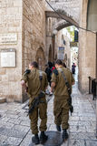 Israeli soldiers Jerusalem. JERUSALEM, ISRAEL - JAN 23, 2011: Two armed Israeli soldiers walking through one of the many alleys in the Old City of Jerusalem Royalty Free Stock Photography