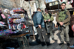 Israeli Soldiers in Jerusalem's Old City. EAST JERUSALEM - JANUARY 7: Israeli Border Police soldiers stop a Palestinian pedestrian and inspect his identity royalty free stock photos
