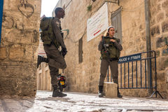 Israeli soldiers - man and woman - guarding Jerusalem. Jerusalem, Israel - November 3, 2015: Israeli soldiers - man and woman - guarding one of the mai street in Royalty Free Stock Photography