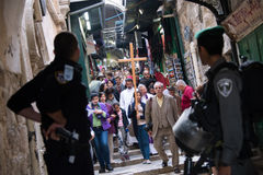 Israeli soldiers and Palestinian Christians in Jerusalem. Israeli soldiers and police watch as Palestinian Christians carry a cross from Redeemer Lutheran Church stock photo