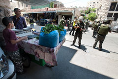 Israeli Soldiers and Palestinians. HEBRON, OCCUPIED PALESTINIAN TERRITORIES - JULY 12: Palestinian vegetable vendors navigate among heavily armed Israeli stock image