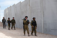Israeli Soldiers and Separation Barrier. AL-WALAJA, OCCUPIED PALESTINIAN TERRITORIES - NOVEMBER 13: Israeli soldiers stand in front of the Israeli separation Royalty Free Stock Photography