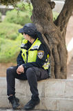 Israeli woman in police. Uniform sitting on the parapet in city of Jerusalem Royalty Free Stock Image