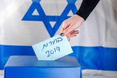 Israeli woman votes at a polling station on election day.Close up of hand. Hebrew text Elections 2019 on Israel flag background. Israeli legislative Elections stock image