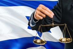Israelischer Richter hält goldene Skalen von Gerechtigkeit mit wellenartig bewegendem Flaggenhintergrund Israels Gleichheitsthema vektor abbildung