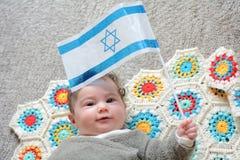 Israelisches neugeborenes Baby, welches die israelische Flagge hält Stockbilder