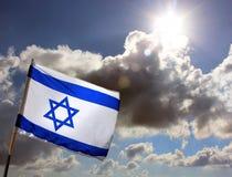Israelisk flagga mot den molniga skyen Arkivfoton
