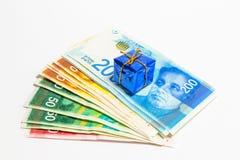 Israelisk pengarbunt av nya israeliska sedlar av olikt värde i siklar NIS med en dekorativ blå ask som föreställer en gåva, I Arkivbilder