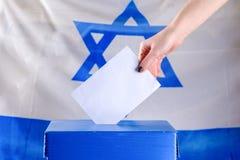 Israelisk ung kvinna som sätter en sluten omröstning i en valurna på valdag royaltyfria foton