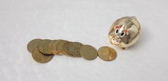 Israeliska mynt på den vita tabellen nära den guld- skinande spargrisen royaltyfri foto