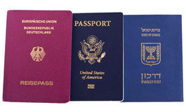 Triple Nationality - Israeli, American & German. Israli, USA and German passports isolated on white background. The USA passport has a biometric chip embeded in Stock Image