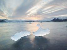 Isstora bitar på Jokulsarlon den is- lagun på solnedgången i Island Arkivfoton