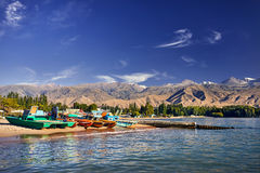 Issyk Kul Lake. Colorful Old school boats and catamarans on the beach of Issyk Kul Lake in Kyrgyzstan stock image