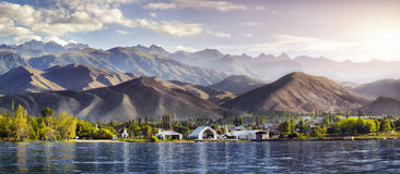 Issyk Kul lake panorama. View to Ruh Ordo cultural complex near Issyk Kul lake at mountains background in Cholpon Ata, Kyrgyzstan royalty free stock photo