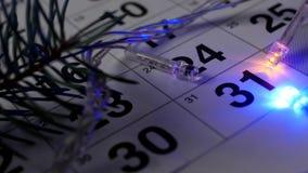 Ist auf dem Tisch der der Dezember-Kalender des neuen Jahres und die Lichter des neuen Jahres brennen um das Datum vom 31. Dezemb stock video