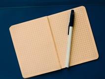 ist auf dem Tisch ein Notizbuch mit einem Stift auf einem blauen Hintergrund Lizenzfreie Stockfotografie