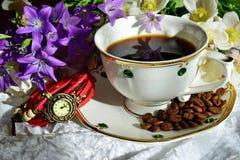 Ist auf dem Tisch ein weißer Tasse Kaffee auf einem Hintergrund von Blumen Auf der Untertasse sind Kaffeebohnen Frühlingsmorgen?  stockbilder