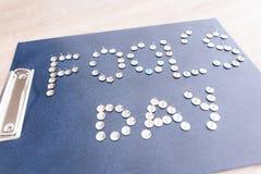 Ist auf dem Tisch eine Tablette für Papiere mit dem Aufschrift Dummkopf-Tag von den kanzleimäßigen Knöpfen Stockbilder