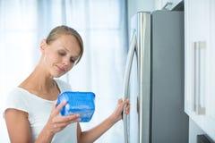 Ist dieses noch fein? Hübsche, junge Frau in ihrer Küche stockfotografie