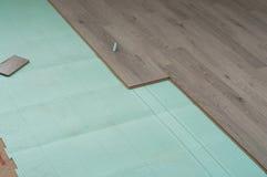 Istalation del nuevo suelo laminado, usando un material de aislamiento de sonidos fotos de archivo libres de regalías