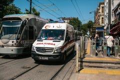 Istambul, o 15 de junho de 2017: Ambulância e urbano sobre o metro à terra que senta-se próximos um do outro no meio do dia Fotos de Stock Royalty Free