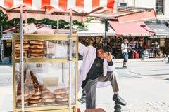 Istambul, o 15 de junho de 2017: Forçado para fora e vendedor virado do produto da padaria da rua que tem a dor de cabeça má Imagens de Stock Royalty Free