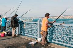 Istambul, o 15 de junho de 2017: Muitos pescadores da população local estão na ponte e nos peixes de Galata O tradicional Imagens de Stock
