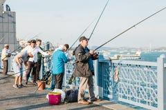 Istambul, o 15 de junho de 2017: Muitos pescadores da população local estão na ponte e nos peixes de Galata O tradicional Imagens de Stock Royalty Free