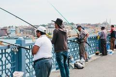 Istambul, o 17 de junho de 2017: Passatempo turco tradicional da pesca Muitos povos estão pescando na ponte de Galata Vida ordiná Imagens de Stock