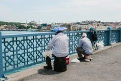 Istambul, o 17 de junho de 2017: Passatempo turco tradicional da pesca Muitos povos estão pescando na ponte de Galata Vida ordiná Fotografia de Stock