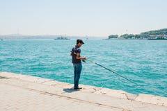 Istambul, o 17 de junho de 2017: Passatempo turco tradicional da pesca Um pescador local está pescando na costa Vida ordinária de Fotografia de Stock Royalty Free