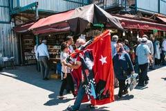 Istambul, o 16 de junho de 2017: Rua turca justa - os povos vendem lembranças do turista nas tendas, nas bandeiras e nos petiscos Imagem de Stock