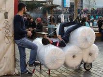 ISTAMBUL, TURQUIA - 28 DE DEZEMBRO DE 2015: Meninos de entrega novos que têm um resto em seu pacote no distrito de Eminonu, no la Imagem de Stock Royalty Free
